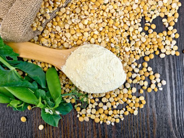 Flour pea in a spoon, yellow flakes in a bag and fresh pods on a background of wooden boards